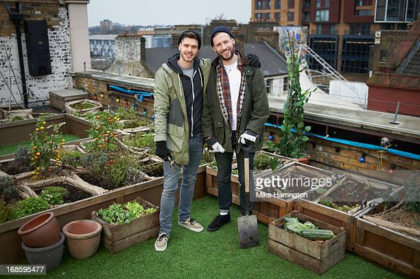 Men in roof garden smiling to camera.