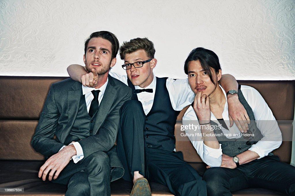 Men in suits talking in nightclub : Stock Photo