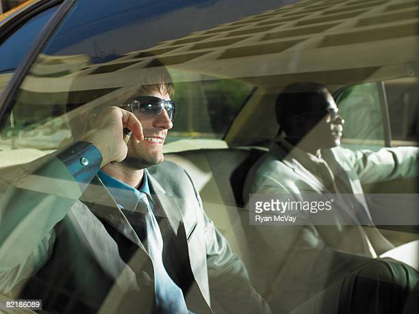 2 men in taxi, one on cell phone