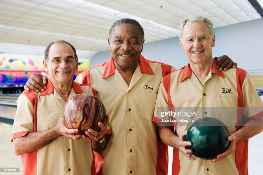 Men in team uniforms holding bowling balls
