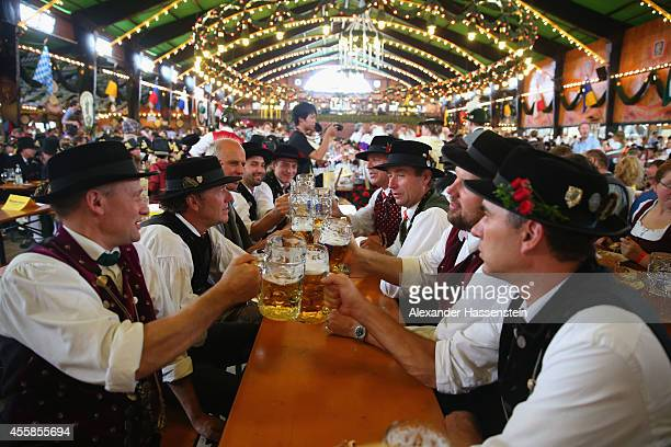 Men in their traditional Bavarian clothing clink beer mugs after the Parade of Costumes and Riflemen on the second day of the 2014 Oktoberfest at...