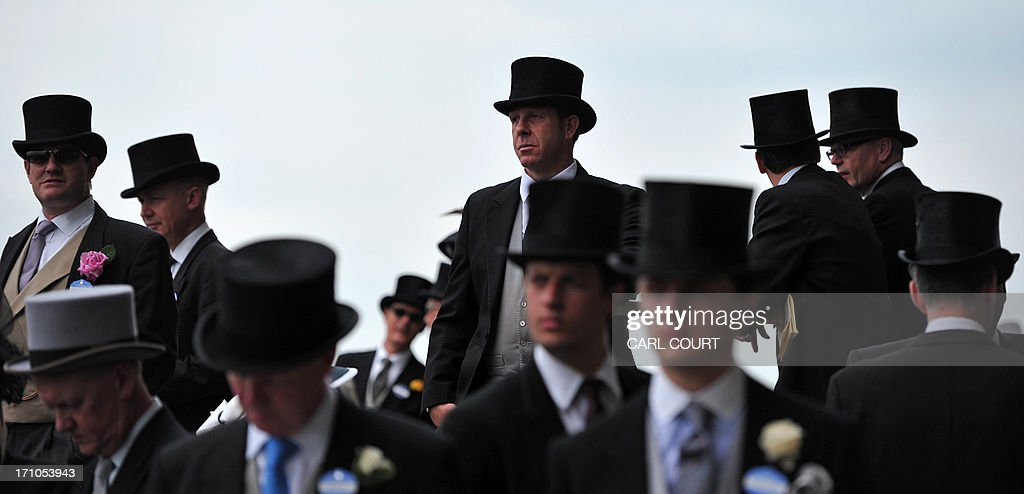 Men in top hats are seen in the royal enclosure on the fourth day of the horse racing festival at Royal Ascot in Berkshire, west of London, on June 21, 2013. Horse racing has been held at the famous Berkshire course since 1711 and tradition is a hallmark of the meeting. Top hats and tails remain compulsory in parts of the course while a daily procession of horse-drawn carriages brings the Queen to the course.