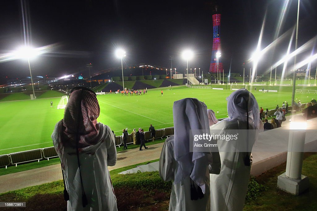 Men in traditional clothes view a Bayern Muenchen training session at the ASPIRE Academy for Sports Excellence on January 2, 2013 in Doha, Qatar.