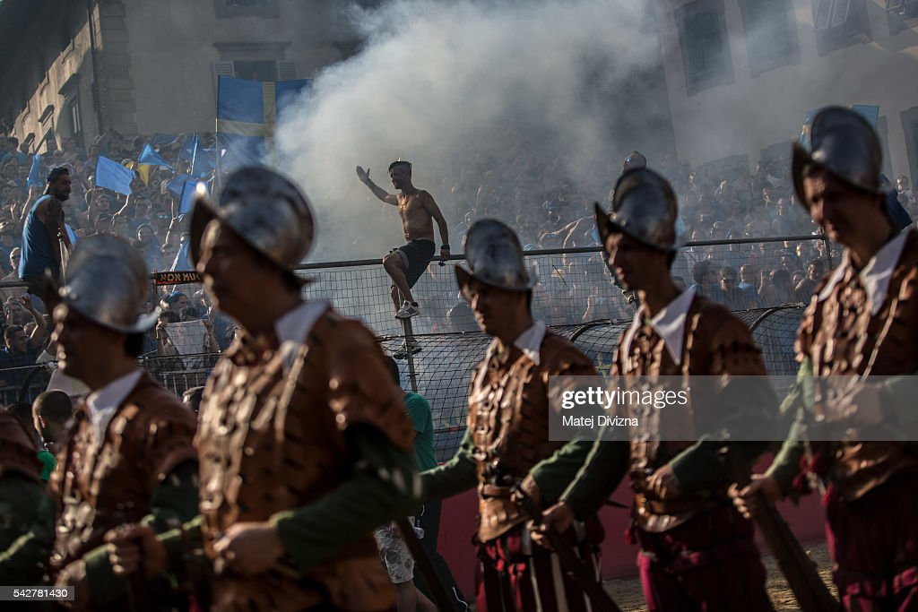 Men in traditional dress march as supporters of the La Santa Croce Azzuri Team cheer on their team before the final match of The Calcio Storico Fiorentino between the Santo Spirito Bianchi (White) Team and the La Santa Croce Azzuri (Blue) Team at the La Santa Croce square on June 24, 2016 in Florence, Italy. The Calcio Storico (Historical Football in English) Fiorentino is an early form of football, originating in the 1500's. It is a combination of football, rugby and wrestling. Now, annually during a weekend in early June, four teams representing the districts of Florence face each other in the first semi-finals. The winners go to the final, played every year on June 24, the day of the patron of Florence, St. John the Baptist. The official rules of calcio (football) were written for the first time in 1580 by Giovanni de Bardi, a count from Florence. The teams are formed by 27 players and the ball can be played either with hands or feet. Tactics such as punching, elbowing and all martial arts techniques are allowed but kicks to the are forbidden, as are fights of two or more against one. There is a referee, a field master, and six linesmen. The game lasts 50 minutes, and the winning team is the one who scores most points. The playing field is a giant sand pit with a narrow split constructing the goal running the width of each end. The Calcio Storico was not played for 200 years, until its revival in 1930.