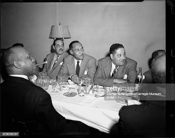 Men including Voyle Parker on left in front of lamp Robert E 'Pappy' Williams in center and Paul F Jones seated with crossed arms on right gathered...