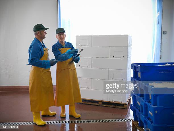 Men inspecting crates of freshly packed fish from hand-reared Scottish salmon farm