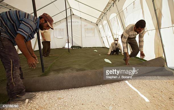 Men install artificial turf in the Save the Children school at the Zaatari Refugee Camp in Jordan