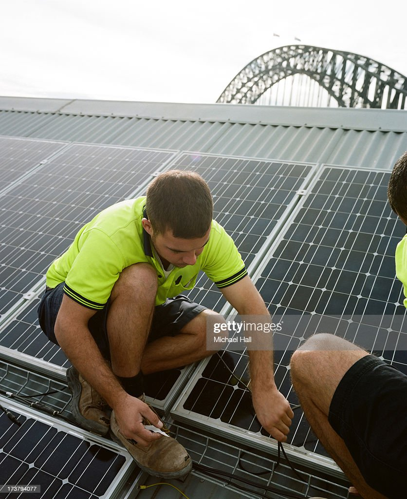 Men installing solar panels on roof : Stock Photo