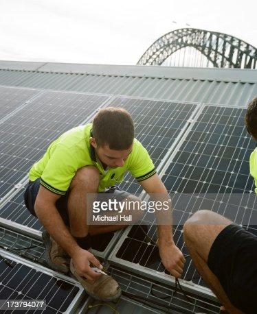 Men installing solar panels on roof : Stock Photo