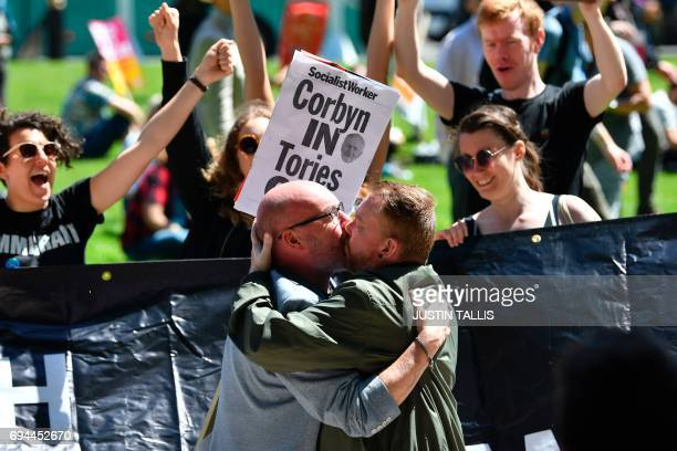Men kiss in front of protesters in Parliament Square in front of the Houses of Parliament in central London on June 10 2017 during a demonstration...