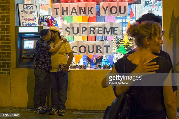 Men kiss near a window display expressing gratitude as people celebrate the Supreme Court ruling on samesex marriage on June 26 2015 in West...