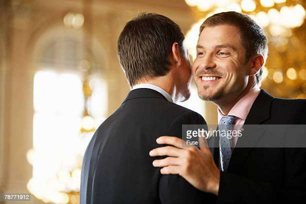 Men Kissing One Another on the Cheek