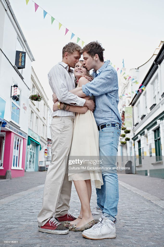 Men kissing woman on city street : Stock Photo