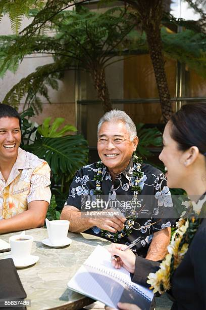 Men laughing with businesswoman at table