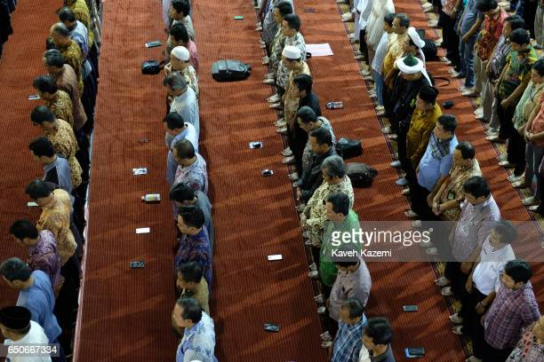 Men lay their smartphones in front of them while they stand praying in Istiqlal Mosque on a Friday on November 25 2016 in Jakarta Indonesia Istiqlal...