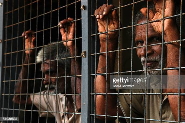 Men lean on the fence at a refugee camp for tsunami survivors January 8 2005 in Matara Sri Lanka Two of the schools in town have turned been turned...