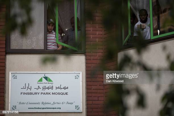 Men lean out the Mosque window as people attend a vigil outside Finsbury Park Mosque on June 19 2017 in London England Worshippers were struck by a...