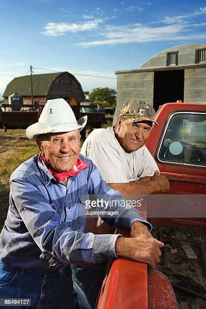 Men leaning on pickup truck smiling