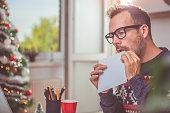 Men wearing blue sweater licking envelope