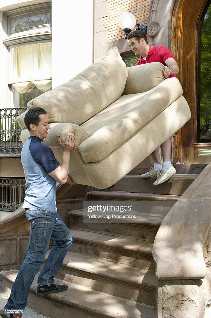 Men lifting and moving couch up stairs to new home