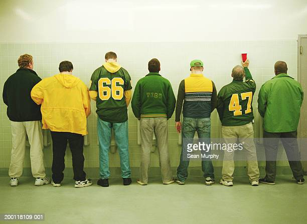 Men lined up at urinal, rear view