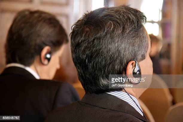Men listening to a simultaneous translation receiver at the Americas Conference at Biltmore Hotel