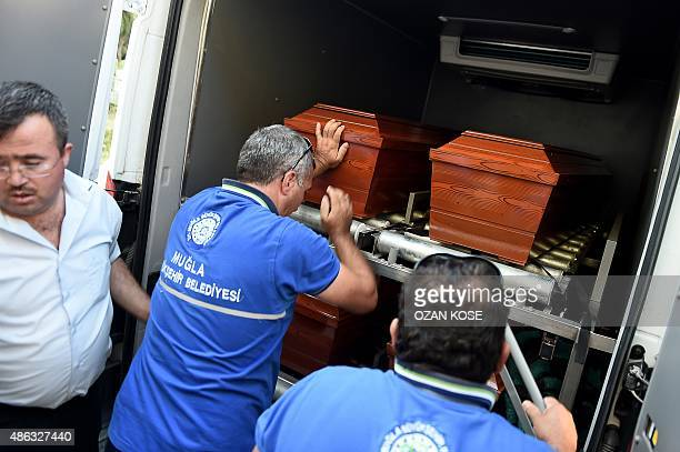 Men load onto a funeral vehicle the coffins of migrants and threeyear old Aylan Kurdi a Syrian boy whose body was washed up on a Turkish beach after...