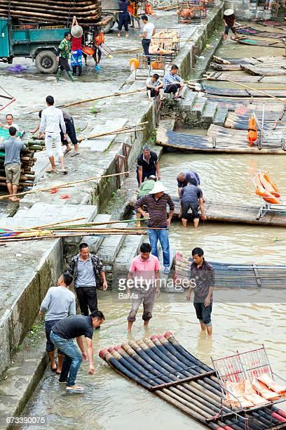 Men loading bamboo rafts on trucks
