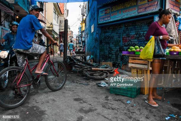 Men look at a demonstration by residents of Rio de Janeiro's Jacarezinho and Manguinhos favelas demanding peace in Rio Brazil on August 20 2017 In...