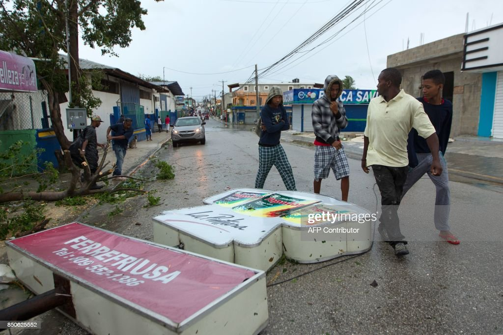 Men look at a sign knocked down by strongs winds in Punta Cana, in the eastermost tip of the Dominican Republic as Hurricane Maria passes north of the La Espanola island the country shares with Haiti, on September 21, 2017. After cutting a devastating path across Puerto Rico, the now Category Three storm, packing 115 mile (185 kilometre) per hour winds, is passing north of the Dominican Republic as it moves toward the Turks and Caicos Islands, according to the US National Hurricane Centre. / AFP PHOTO / Erika SANTELICES
