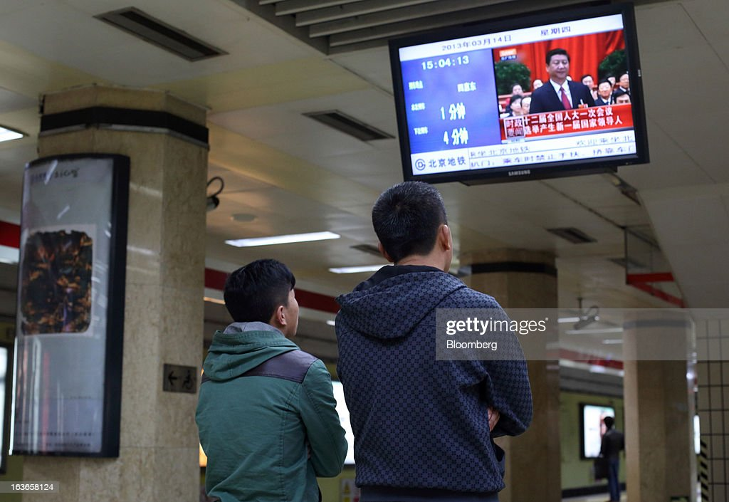 Men look at a television monitor displaying an image of Xi Jinping, newly named president of China, during a news broadcast at a subway station in Beijing, China, on Thursday, March 14, 2013. Xi was named China's president by the national legislature, replacing Hu Jintao in the country's most rapid formal transfer of power in more than a generation. Photographer: Tomohiro Ohsumi/Bloomberg via Getty Images