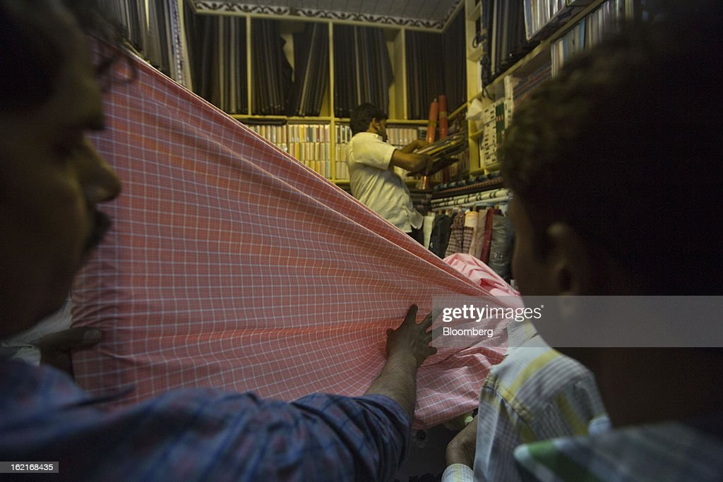 Men look at fabric at a store in the Burrabazar area of Kolkata, India, on Tuesday, Feb. 19, 2013. India's slowest economic expansion in a decade is limiting profit growth at the biggest companies even as foreigners remain net buyers of the nation's stocks, according to Kotak Institutional Equities. Photographer: Brent Lewin/Bloomberg via Getty Images