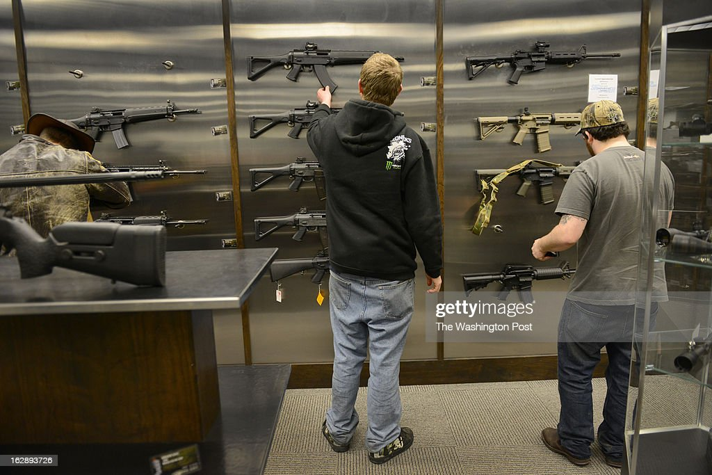 Men look at semiautomatic rifles for sale at the SIG Sauer Academy pro shop in Exeter NH on January 30 2013 The company has a pro shop and training...