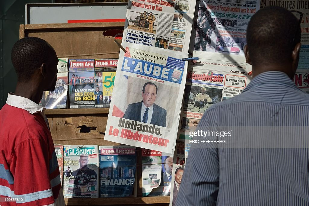 Men look at the front pages of newspapers on January 21, 2013 in a street of Bamako. French and Malian troops recaptured the key towns of Diabaly and Douentza on Monday in a major boost in their drive to rout Al Qaeda-linked rebels holding Mali's vast arid north.