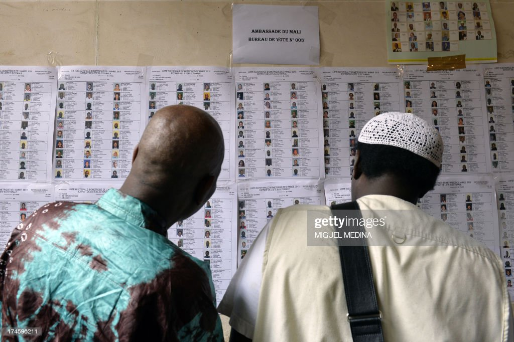 Men look at the list of biometric voters at the Malian embassy in Paris on July 28, 2013 during the Malian presidential elections. Malians voted today for a president expected to usher in a new dawn of peace and stability in the conflict-scarred nation. They have a choice of 27 candidates as they vote for the first time since last year's military coup upended one of the region's most stable democracies, as Islamist militants hijacked a separatist uprising to seize much of the country. AFP PHOTO / MIGUEL MEDINA