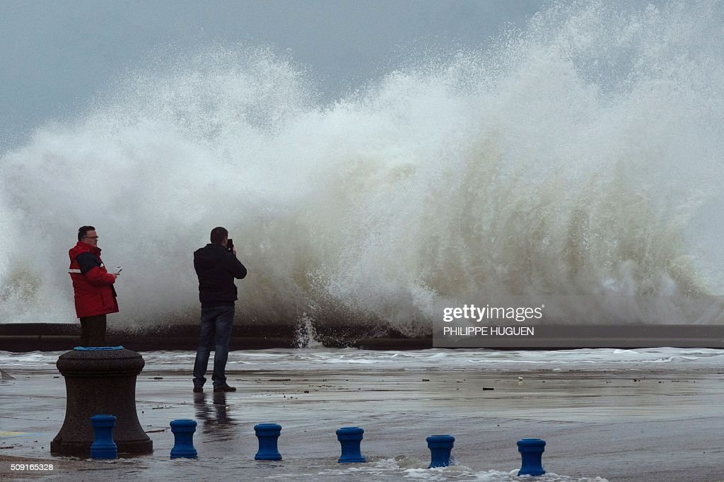 Men look at waves breaking against the Wimereux breakwater, northern France, on February 9, 2016. High winds buffeted northwestern Europe on February 8, leaving one woman in France in a coma after she was hit by an advertising hoarding. Electricity was cut to 5,000 homes in northern France. / AFP / PHILIPPE HUGUEN