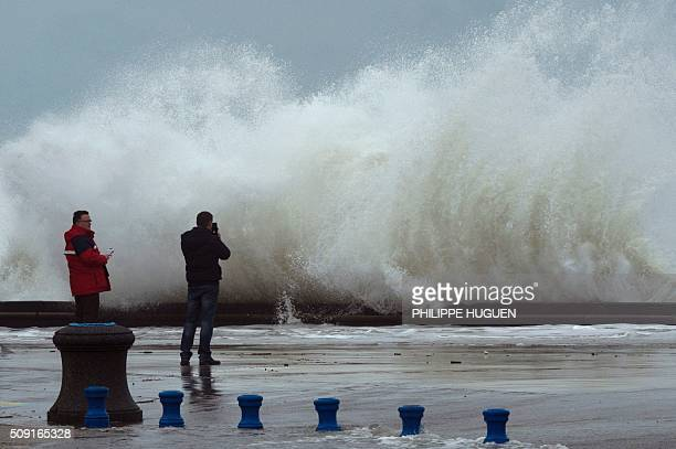 Men look at waves breaking against the Wimereux breakwater northern France on February 9 2016 High winds buffeted northwestern Europe on February 8...