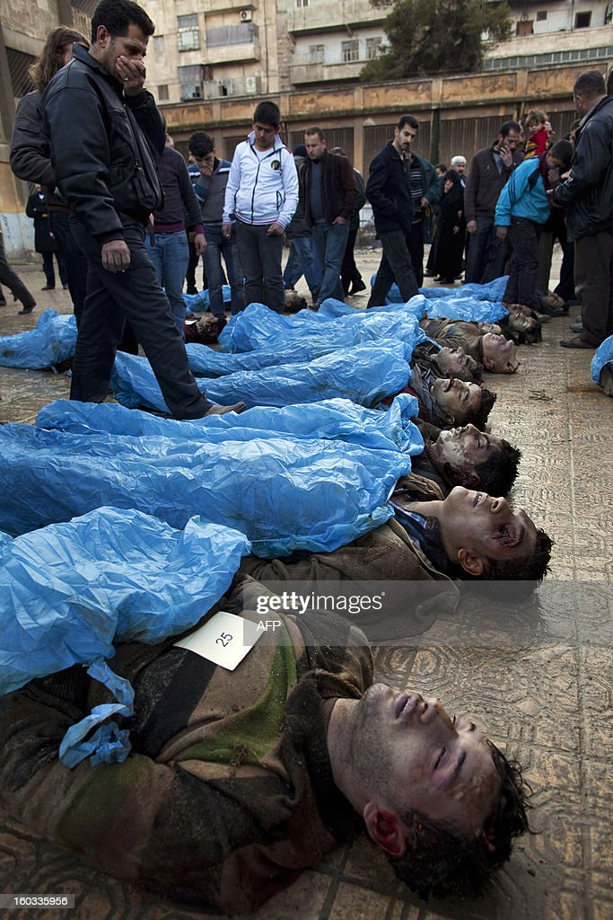 Men look for their relatives amongst the bodies of Syrian civilians executed and dumped in the Quweiq river, in the grounds of the courtyard of a Yarmouk School, in the Bustan al-Qasr district of Aleppo, on January 29, 2013. The bodies of at least 65 young men, all executed with a single gunshot to the head or neck, were found in a river in Aleppo city, adding to the grim list of massacres committed during Syria's 22-month conflict.