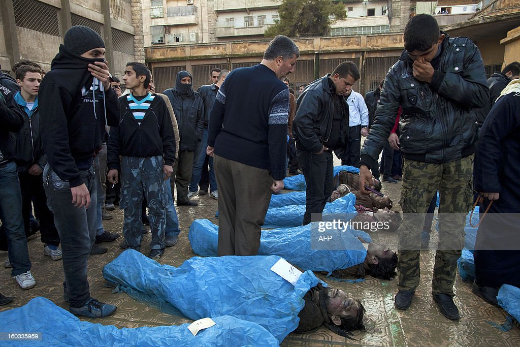 Men look for their relatives amongst the bodies of Syrian civilians executed and dumped in the Quweiq river, in the grounds of the courtyard of a Yarmouk School, in the Bustan al-Qasr district of Aleppo, on January 29, 2013. The bodies of at least 65 young men, all executed with a single gunshot to the head or neck, were found in a river in Aleppo city, adding to the grim list of massacres committed during Syria's 22-month conflict. AFP PHOTO/JM LOPEZ