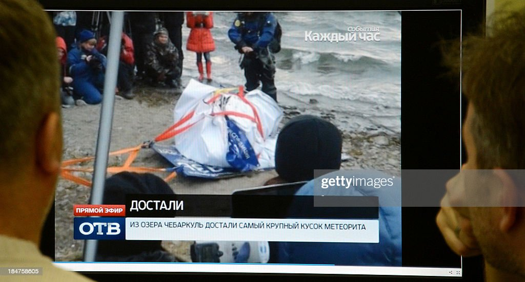 Men look in Moscow on October 16 at a computer screen displaying a team of divers pulling out a 15metrelong suspected meteorite wrapped it in a...