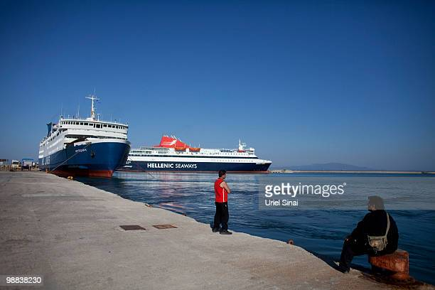 Men look on from the ferry dock on May 1 2010 in Mytilene Greece Independent travel agency Sunvil has stated that Greek tourism will not be affected...