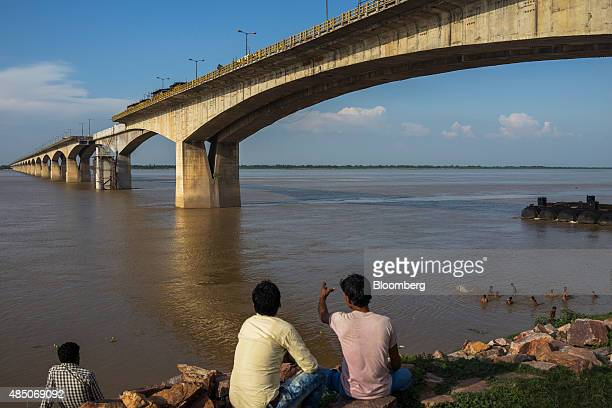 Men look out at the under repair Mahatma Gandhi Setu bridge as people bath in the Ganges river below in Patna Bihar India on Monday July 27 2015 More...