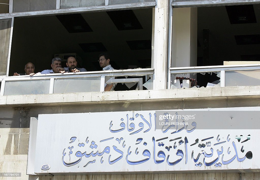 Men look out of the shattered window of a building housing the Wafaq religious authority - Damascus branch, following a blast in the Marjeh district of the capital, on April 30, 2013. The blast killed at least 13 people, Syrian state television reported, a day after a Prime Minister Wael al-Halqi survived a bomb attack elsewhere in the capital .