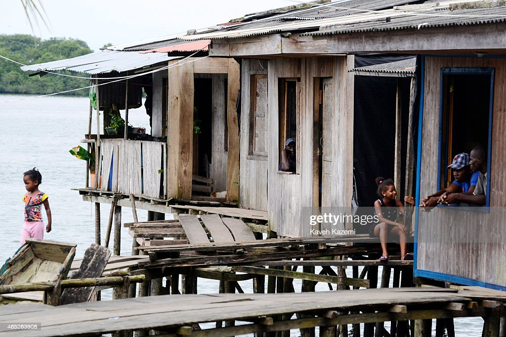 BUENAVENTURA COLOMBIA JANUARY 14 2015 Men look out the window of their wooden house with children seen playing on wooden planks walkway on the sea...