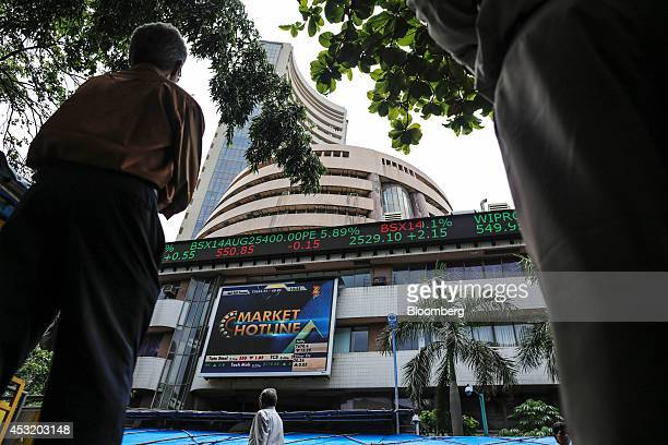 Men look up at an electronic ticker board that indicates stock figures at the Bombay Stock Exchange in Mumbai India on Tuesday Aug 5 2014 Indias...