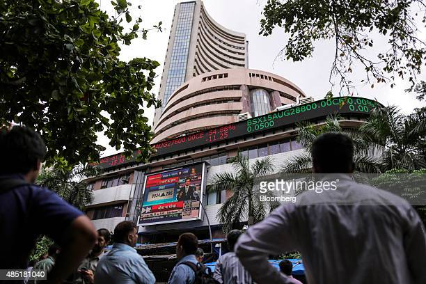 Men look up at an electronic ticker board that indicates stock figures at the Bombay Stock Exchange in Mumbai India on Tuesday Aug 25 2015 Indian...
