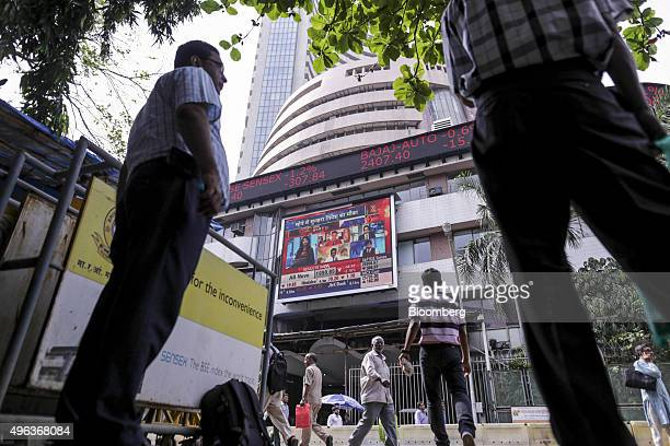 Men look up at an electronic ticker board that indicates stock figures at the Bombay Stock Exchange in Mumbai India on Monday Nov 9 2015 India's...