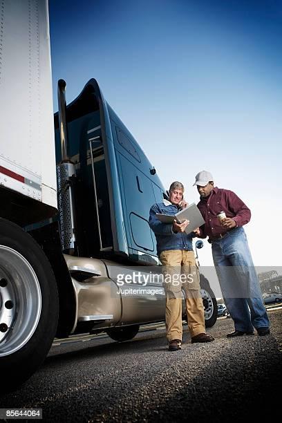 Men looking at paperwork near tractor trailer