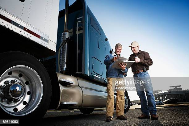 Men looking at paperwork near tractor trailer