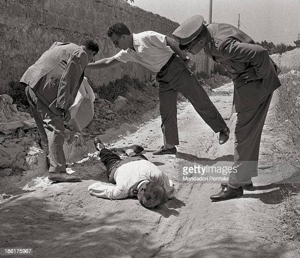 Men looking at the body of Angelo Galatolo who has been killed during the Mafia war for the control of fruit and vegetable markets Sicily 23rd August...